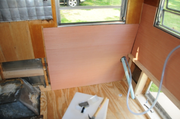 Then we cut the new panel for that wall (the old panel was all water damaged under the window and at the floor) and tacked it in.